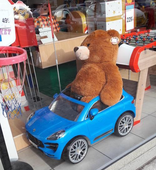 photo d'un ours en peluche immense dans une petite voiture jouet, il dépasse vraiment beaucoup