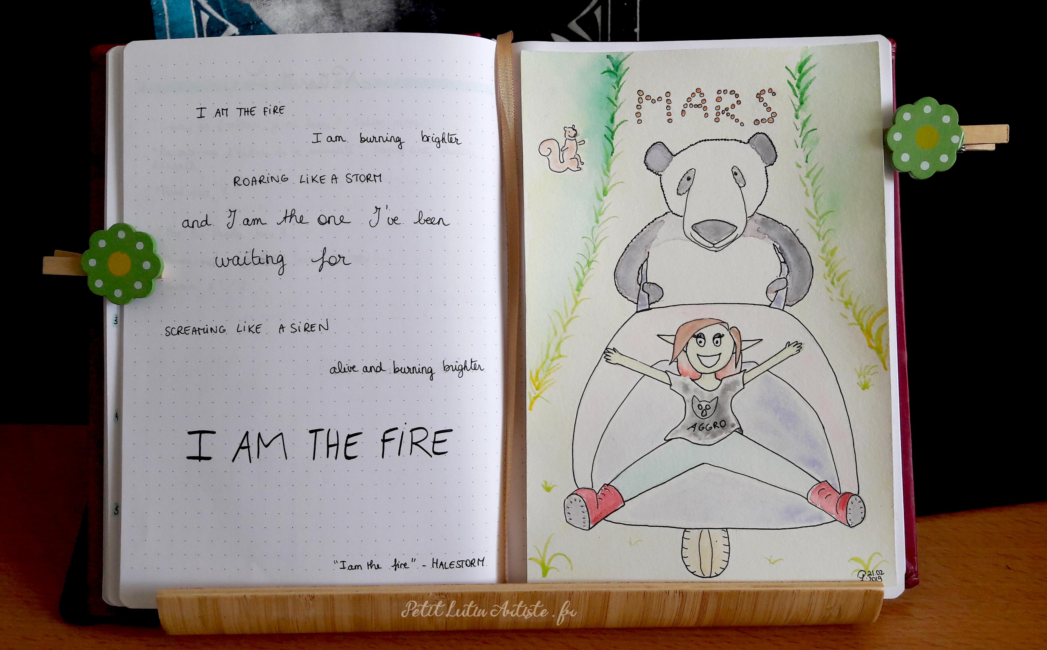 Belette Journal, mon bullet journal de mars 2019, page de gauche le refrain de 'I am the Fire' de Halestorm, à droite une aquarelle avec Moustache le panda qui pousse une brouette dans laquelle est assise Petit Lutin