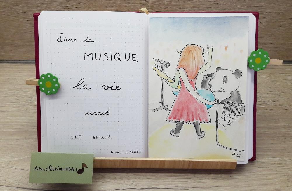 Belette Journal, mon bullet journal de juin 2019, page de gauche j'ai écrit 'Sans la musique, la vie serait une erreur',                          et à droite Moustache le panda prend en photo Petit Lutin alors qu'elle est sur scène et joue de la basse