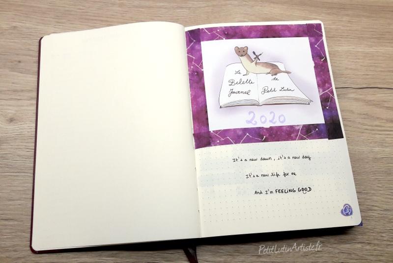 """photo du setup 2020 de mon bullet journal : ma page de garde. j'ai collé ma belette avec du masking tape violet et j'ai écrit en dessous """"it's a new dawn it's a new day, it's a new life for me... and I'm feeling good"""""""