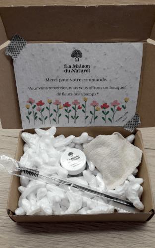 photo unboxing : un petit carton contient un goupillon, le pot de mascara, un khôl dans un mini sachet en tissu, une carte à planter. Des copeaux en polystyrène empêchent les éléments de bouger.